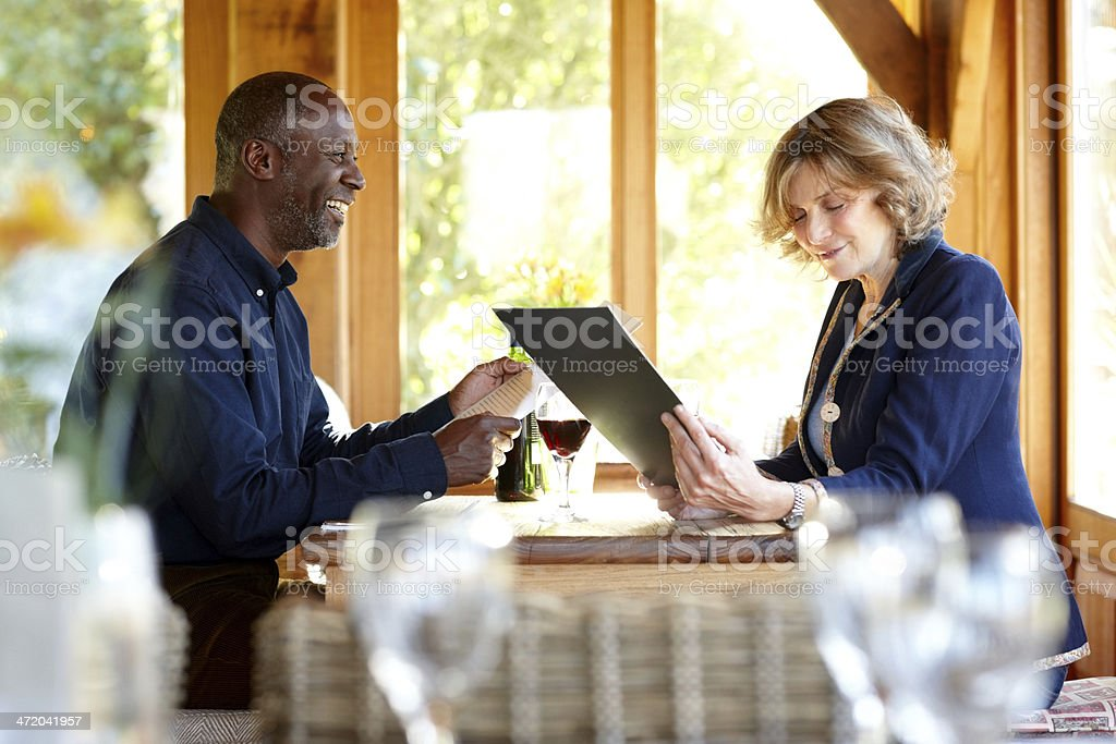 Happy mature couple reading menu in a restaurant stock photo