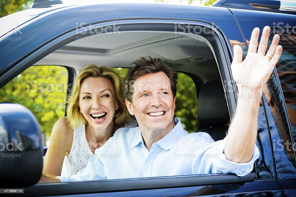 Happy Mature Couple ready to travel in  their car royalty-free stock photo