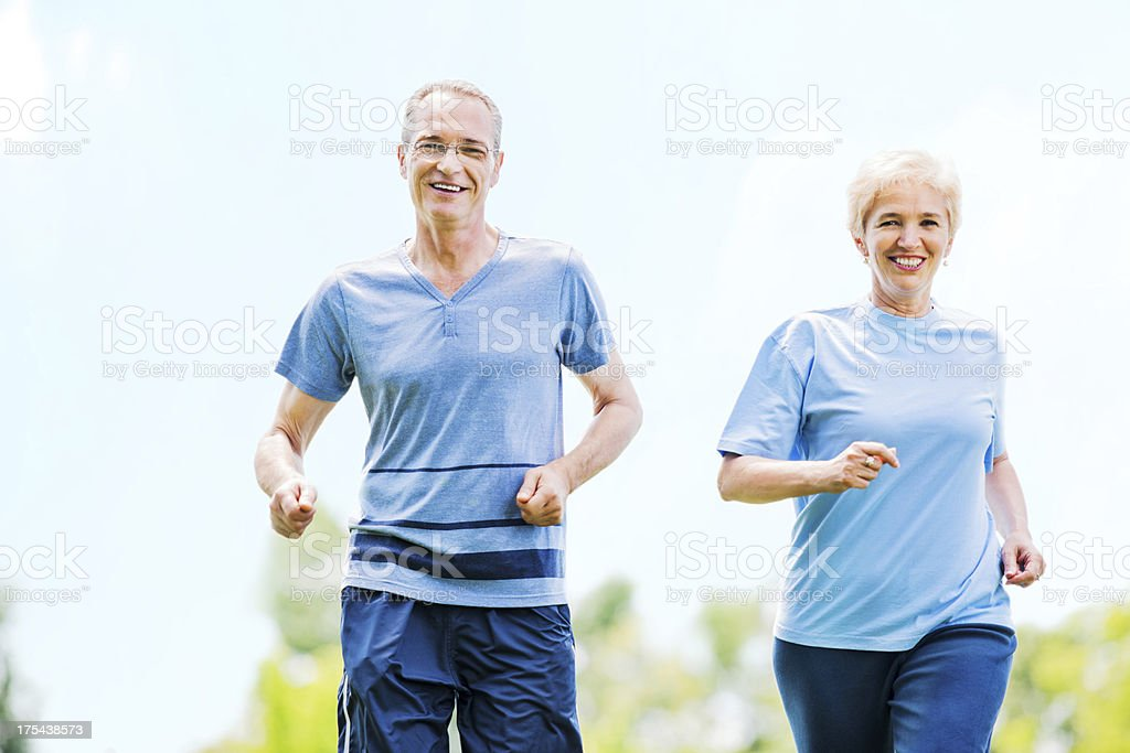 Happy mature couple running in nature. royalty-free stock photo