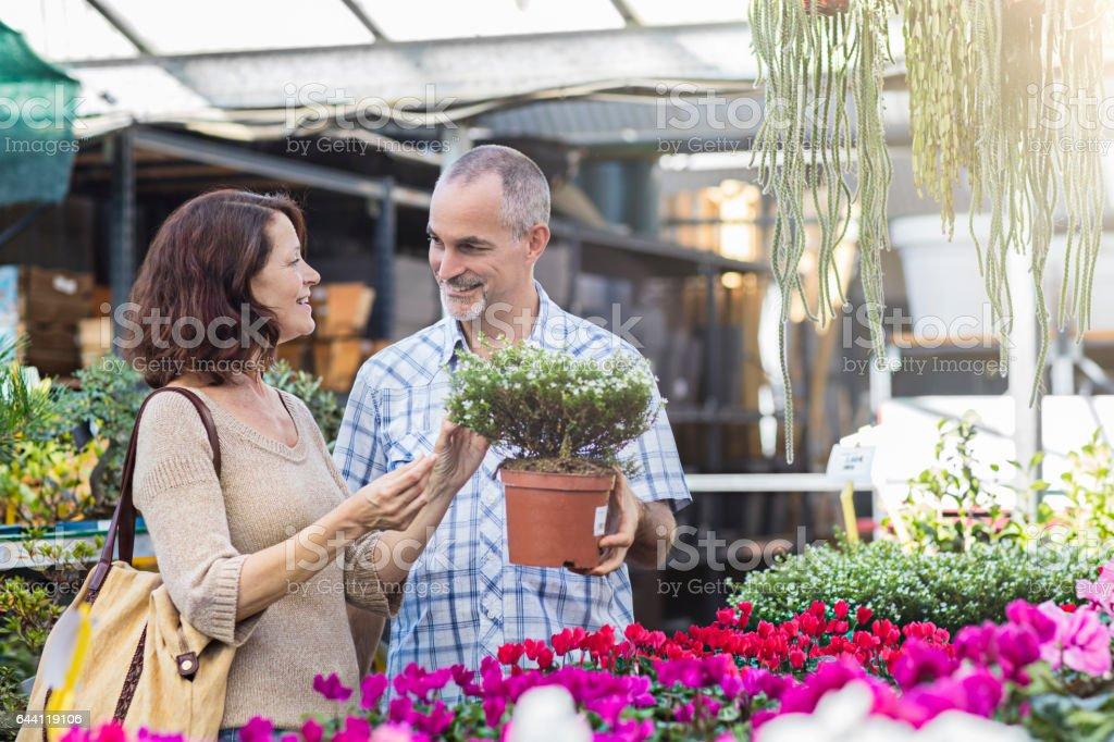 Happy mature couple shopping at plant nursery stock photo