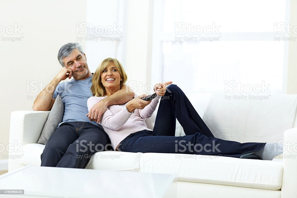 Happy mature couple sitting together watching television royalty-free stock photo