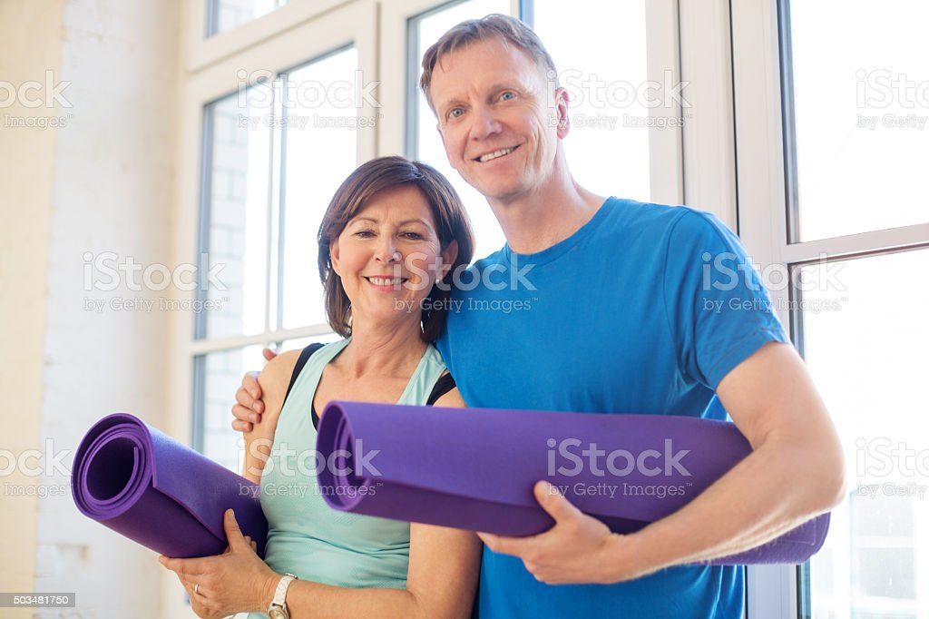 Happy mature couple standing with yoga mats stock photo