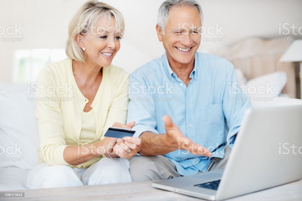 Happy mature couple using credit card to shop online stock photo