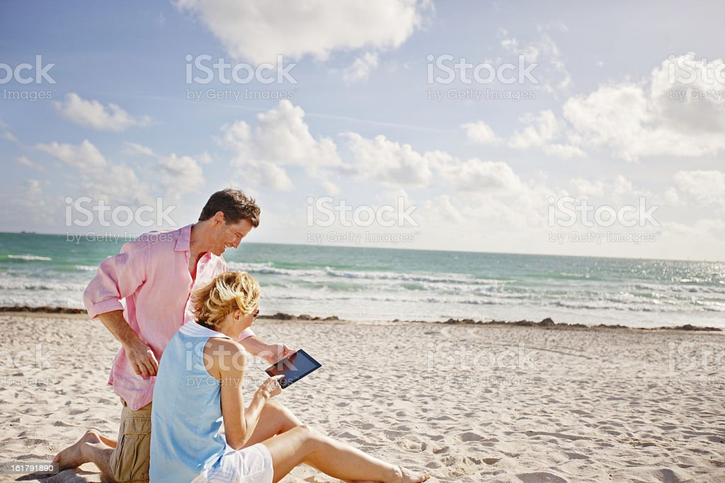 Happy Mature Couple using Digital Tablet on the Beach royalty-free stock photo
