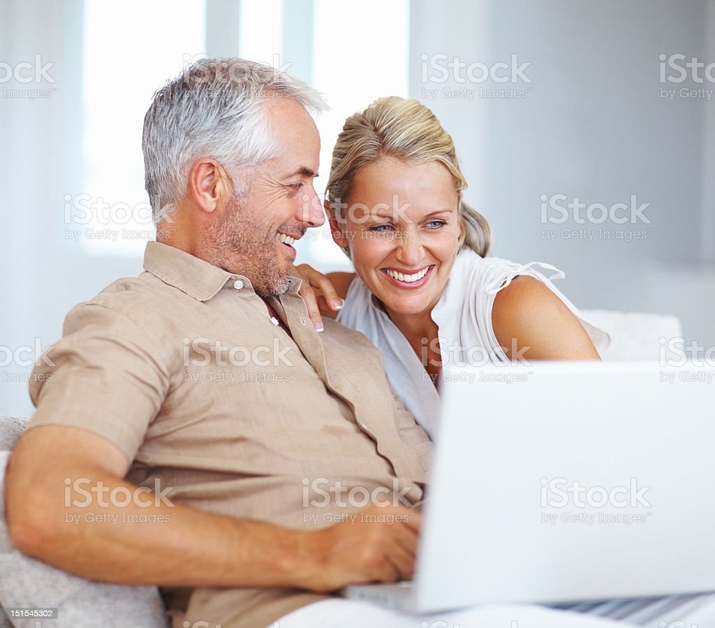 Happy mature couple using laptop at home royalty-free stock photo