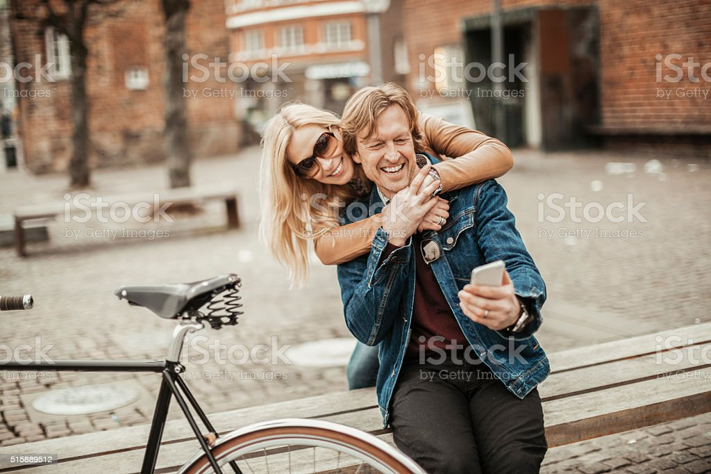 Happy mature couple using mobile phone stock photo
