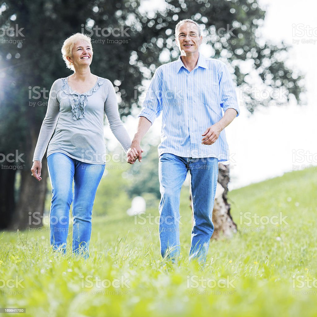 Happy mature couple walking in the field royalty-free stock photo