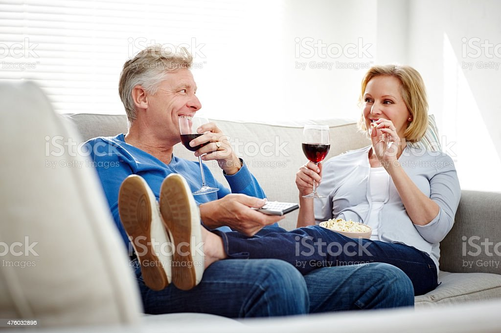 Happy mature couple  watching  television at home stock photo