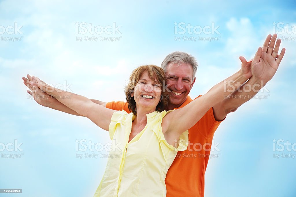 Happy, mature couple with arms stretched out like wings royalty-free stock photo