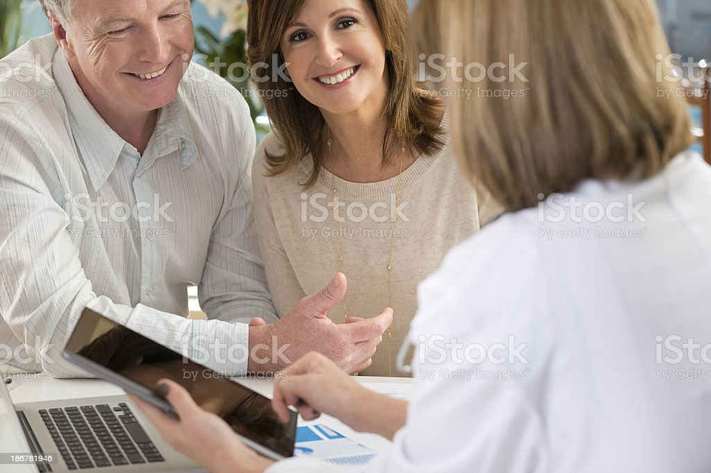 Happy mature couple with doctor using digital tablet royalty-free stock photo