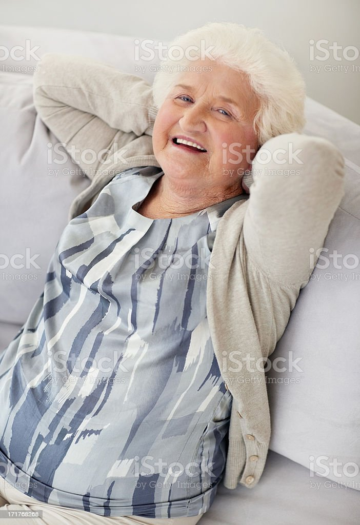 Happy mature female relaxing in sofa with hands behind head stock photo