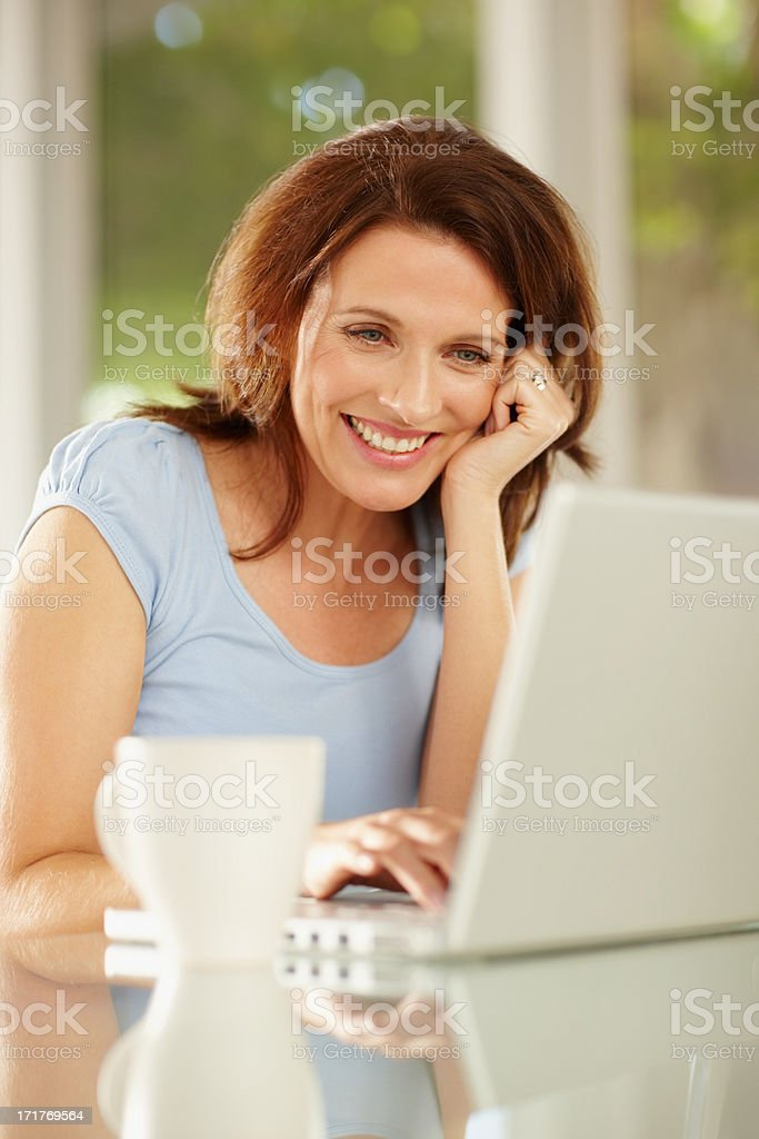 Happy mature female using a laptop royalty-free stock photo