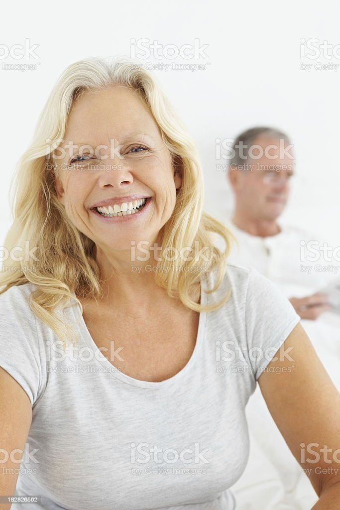 Happy mature female with husband in the background royalty-free stock photo