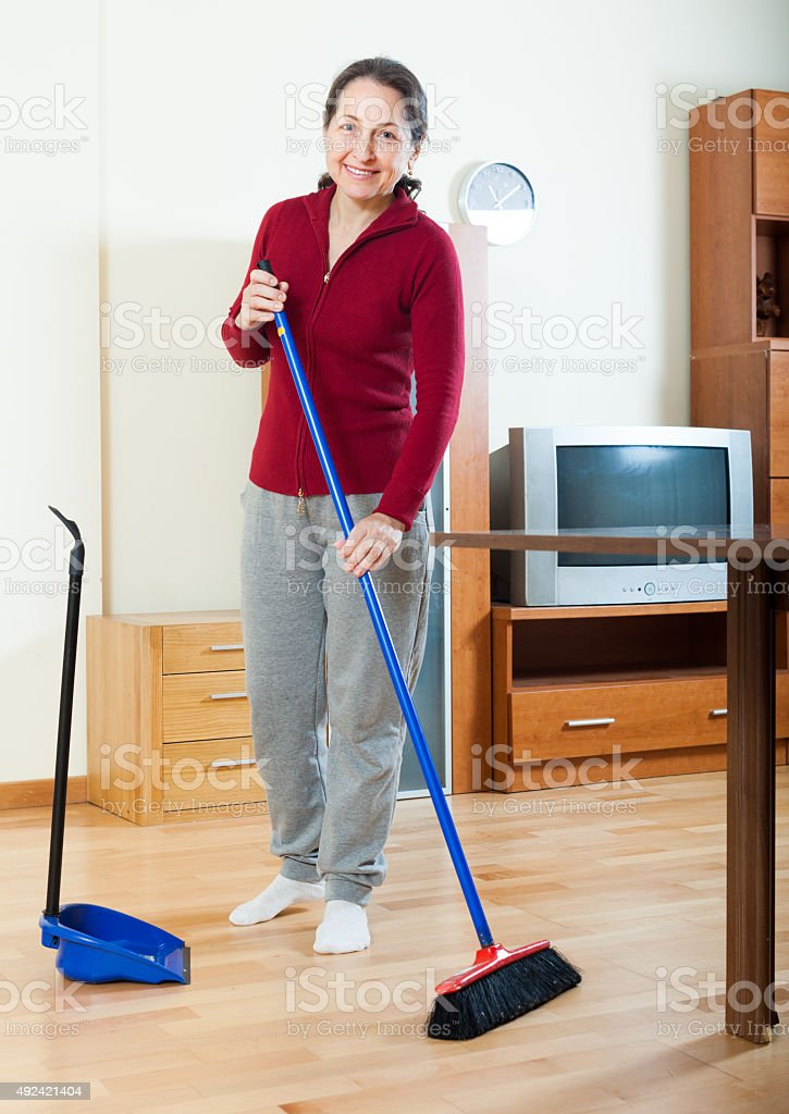 happy mature housewife cleaning with   brush stock photo