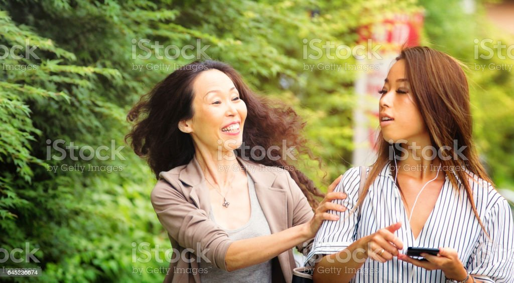 Happy mature Japanese woman interrupts younger friend stock photo