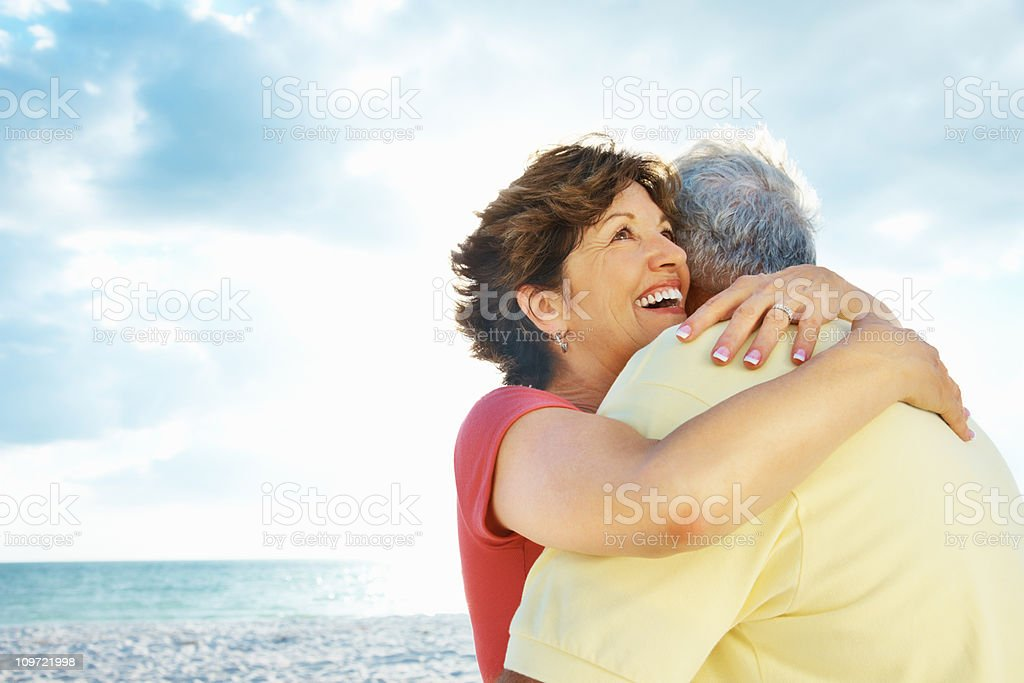 Happy mature lady embracing a man on beach against sea royalty-free stock photo