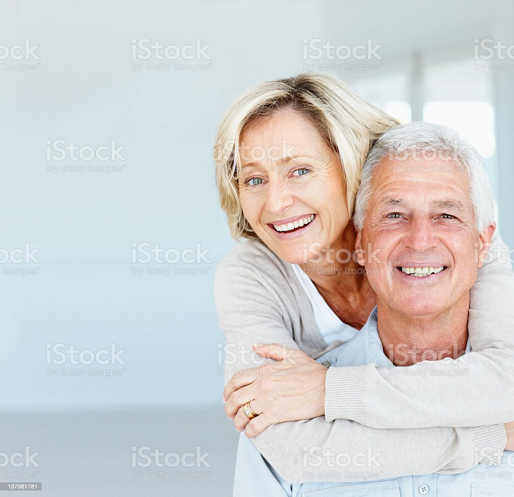 Happy mature lady hugging her husband from behind stock photo