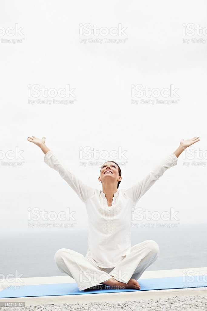 Happy mature lady with arms raised sitting on mat royalty-free stock photo