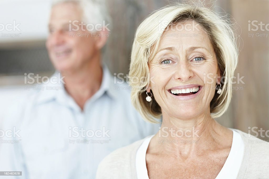 Happy mature lady with husband in the background royalty-free stock photo