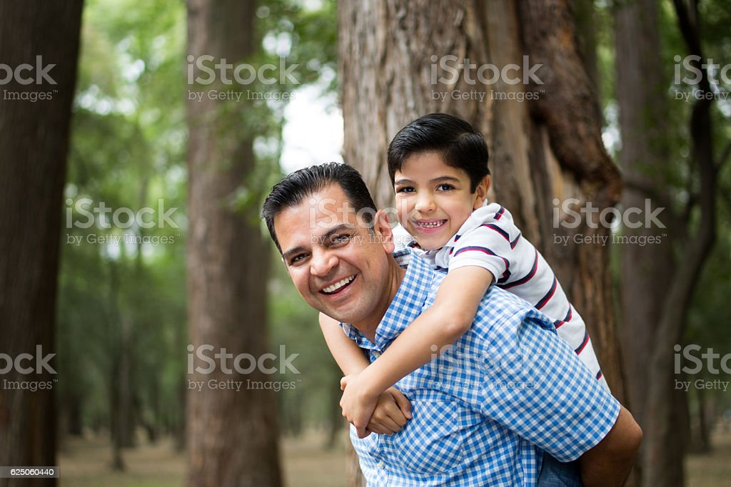 Happy mature latin father carrying son on back stock photo