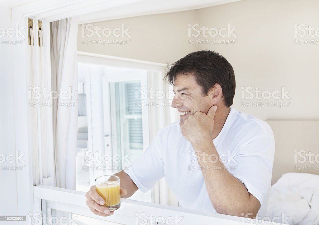 Happy mature man at window holding a glass of juice royalty-free stock photo