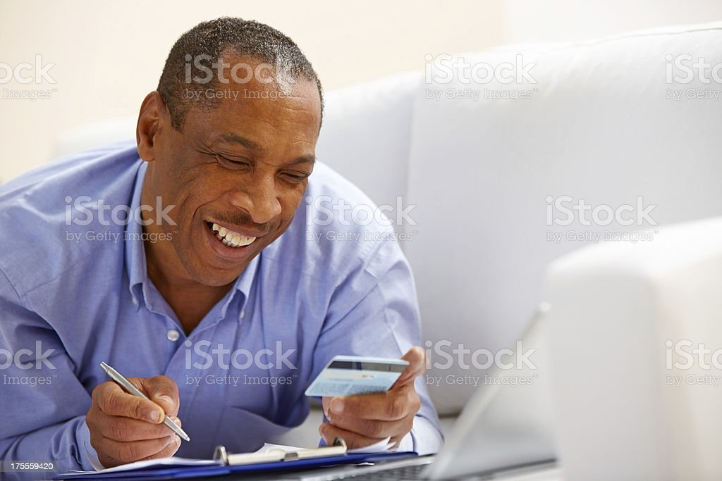 Happy mature man checking credit card bills royalty-free stock photo