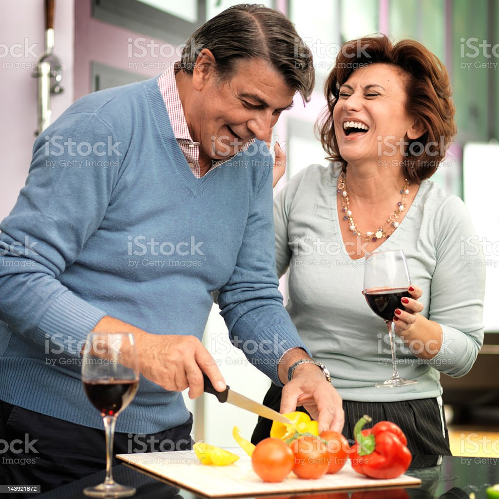 Happy Mature Man Chopping Vegetable And Woman Holding Wine royalty-free stock photo