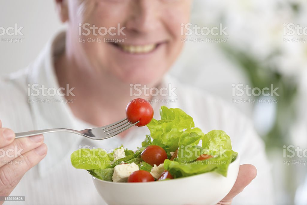 Happy mature man eating salad royalty-free stock photo