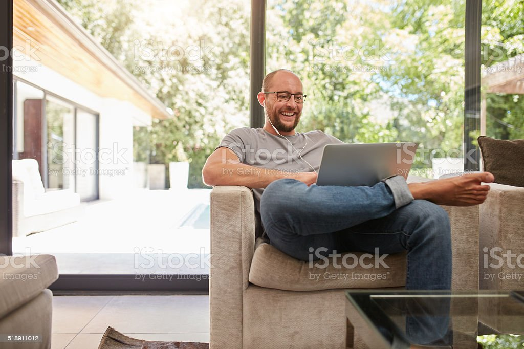 Happy mature man having video call on laptop stock photo