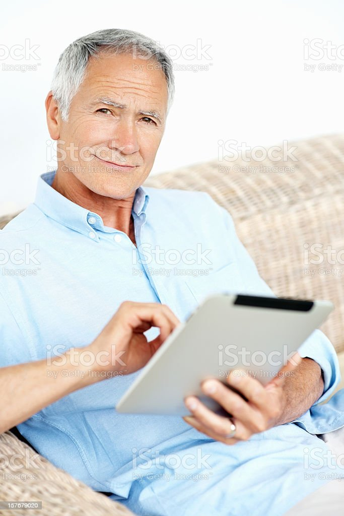 Happy mature man holding a tablet PC against white background stock photo