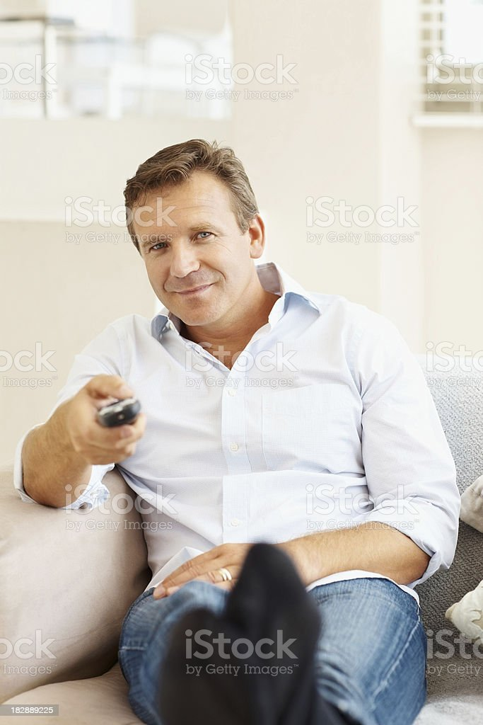 Happy mature man holding remote control at home royalty-free stock photo