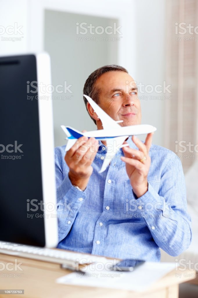 Happy mature man holding toy plane at home royalty-free stock photo