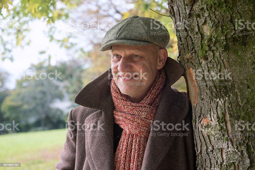 Happy mature man leaning against a tree outdoors. stock photo
