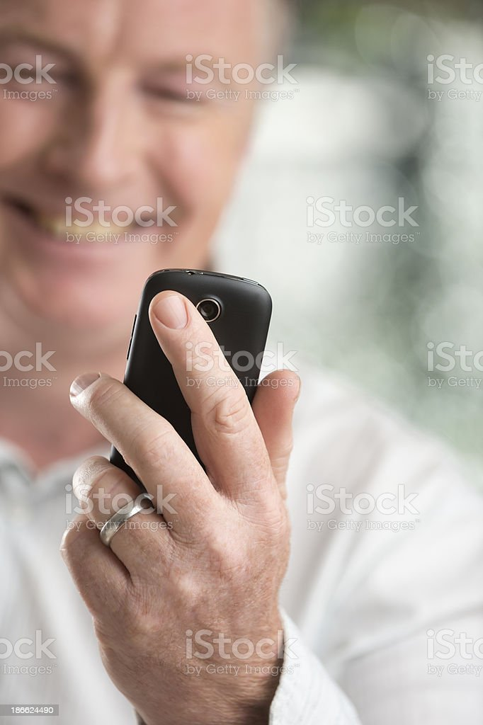 Happy mature man looking at mobile phone royalty-free stock photo