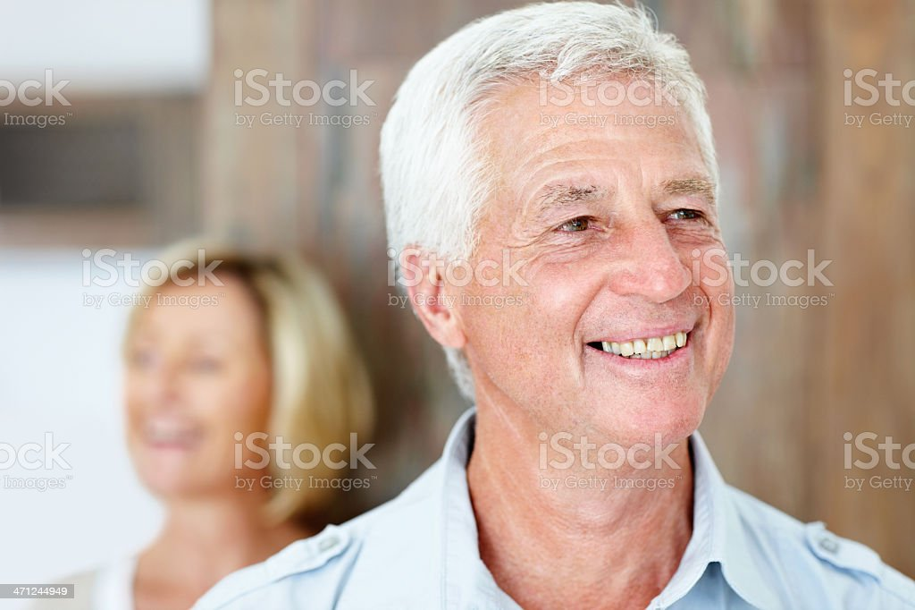 Happy mature man looking away with wife in background royalty-free stock photo