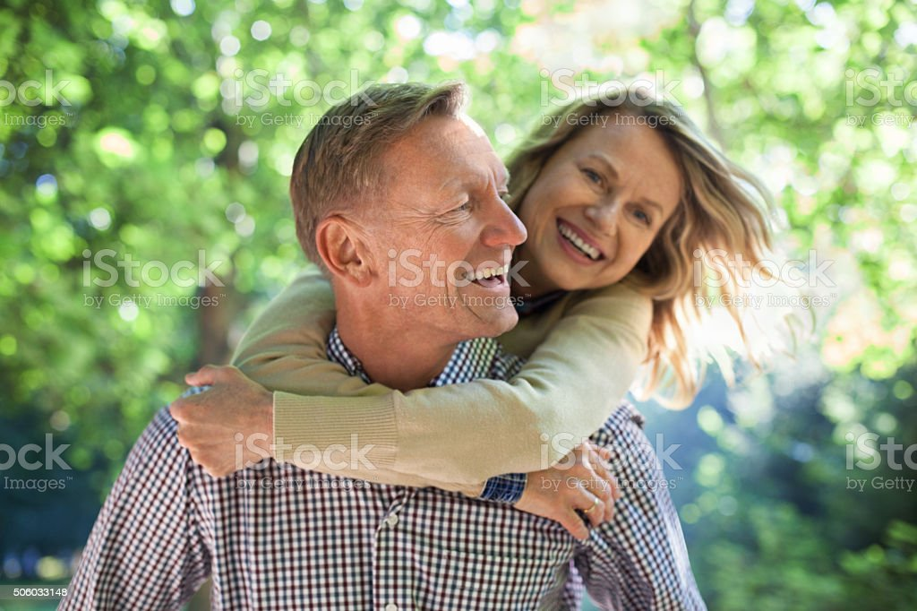 Happy mature man piggybacking his wife in a park stock photo