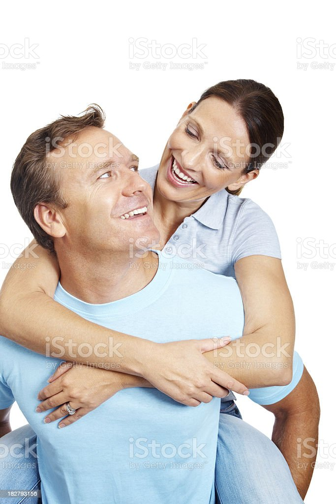 Happy mature man piggybacking wife against white background royalty-free stock photo