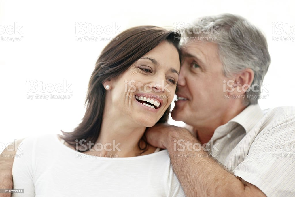 Happy mature man sharing a secret with his wife stock photo