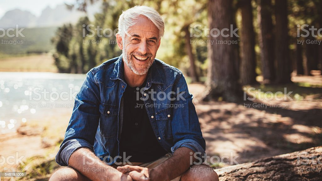 Happy mature man sitting near a lake stock photo