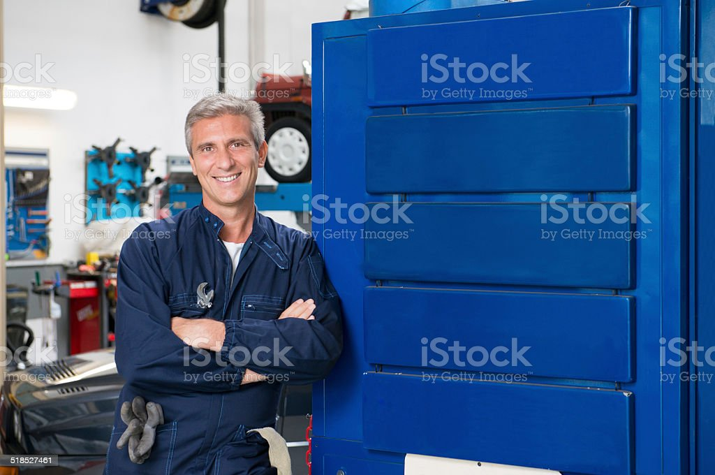Happy Mature Mechanic In Garage stock photo