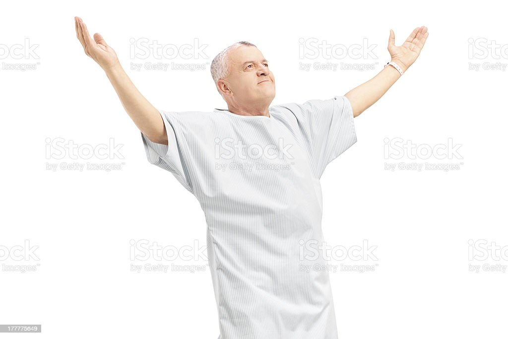 Happy mature patient gesturing happiness with raised hands stock photo