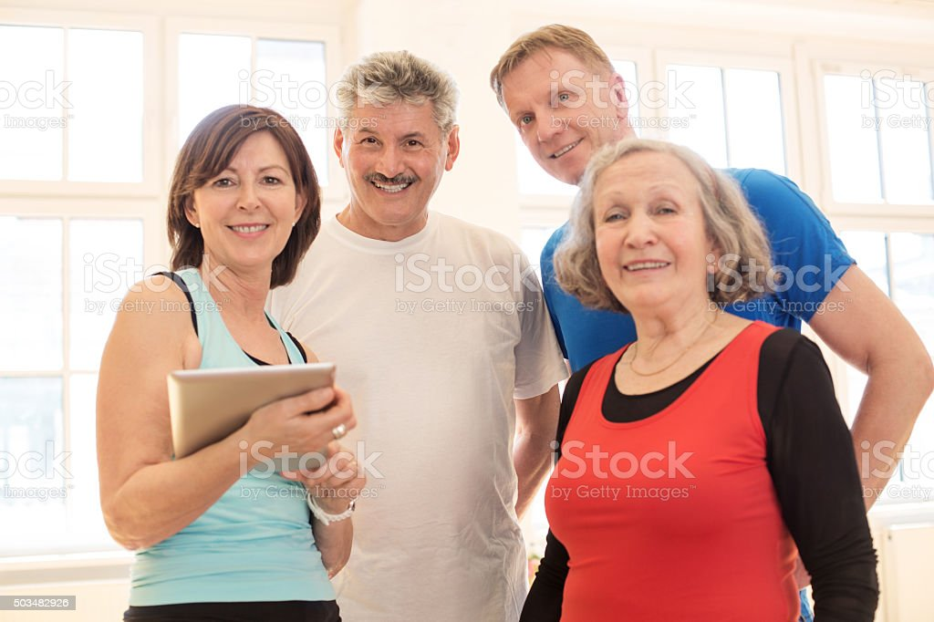 Happy mature people standing together in health club stock photo