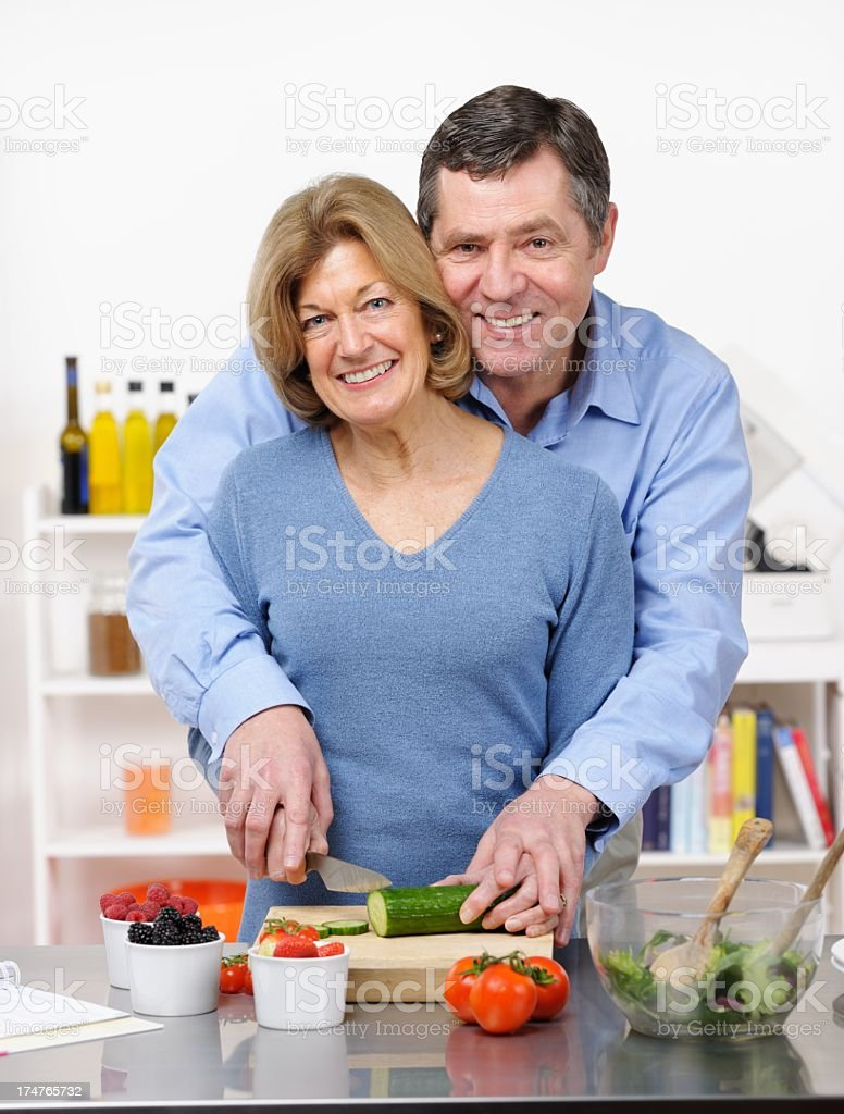Happy Mature/ Senior Couple Slicing Cucumber Together royalty-free stock photo