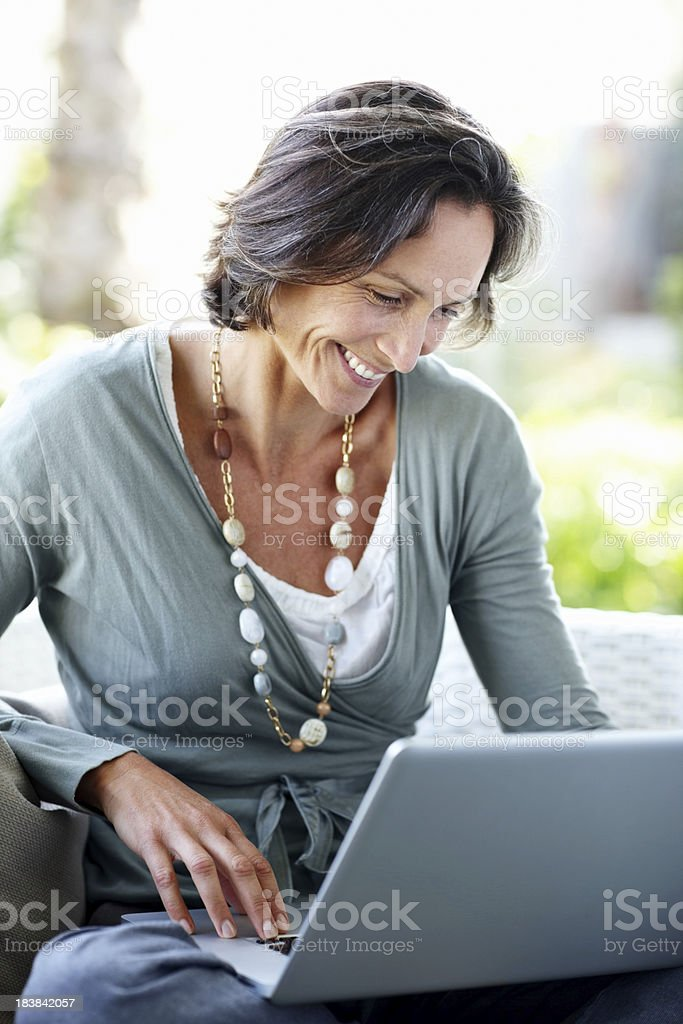 Happy, mature woman at home working on a laptop royalty-free stock photo