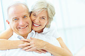 Happy mature woman embracing senior man from behind