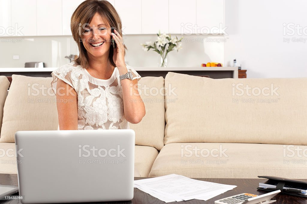 Happy mature woman filling out a document with laptop royalty-free stock photo