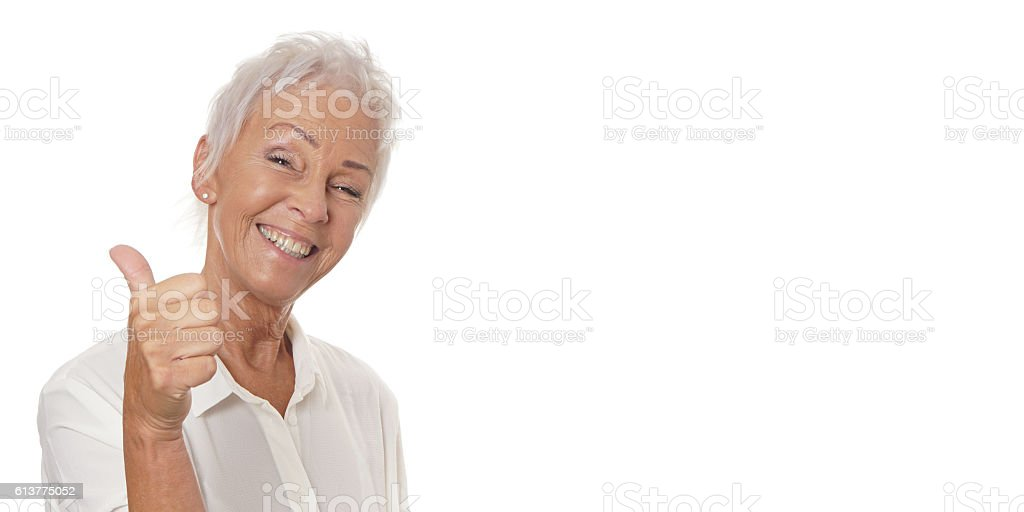 happy mature woman giving thumbs up stock photo