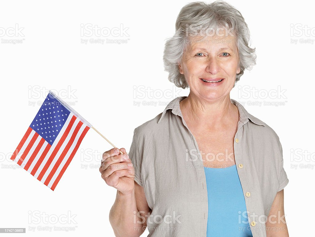 Happy mature woman holding a United States flag against white stock photo