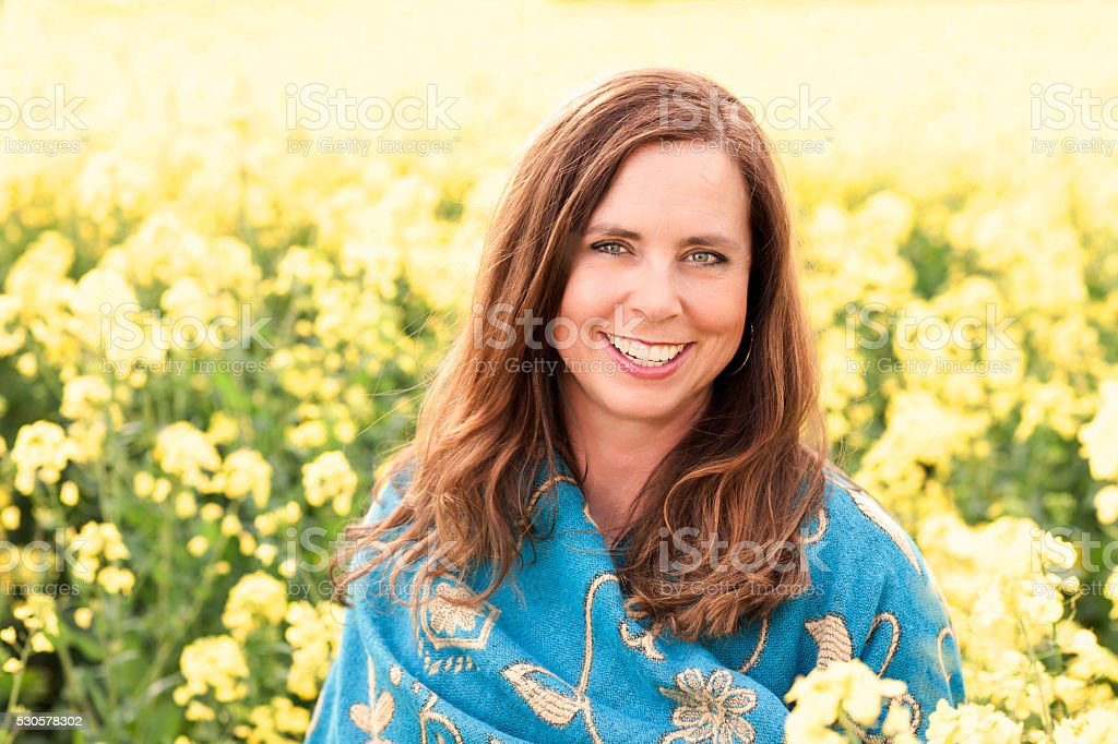 Happy mature woman in yellow field in nature stock photo