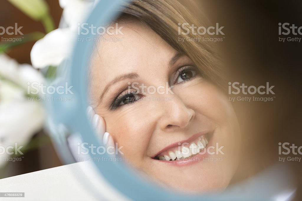 Happy mature woman looking in the mirror stock photo